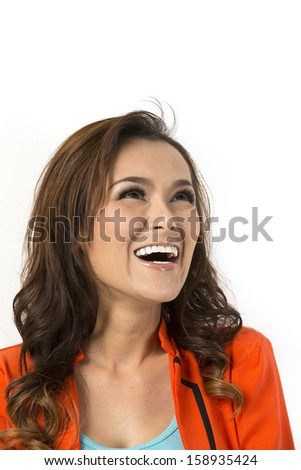 Close up Portrait of a thoughtful Asian woman looking up. Leaning against a white wall. - stock photo
