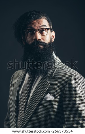 Close up Portrait of a Thoughtful Man with Long Facial Hair, Wearing Formal Suit, Looking Up Seriously on a Black Background. - stock photo
