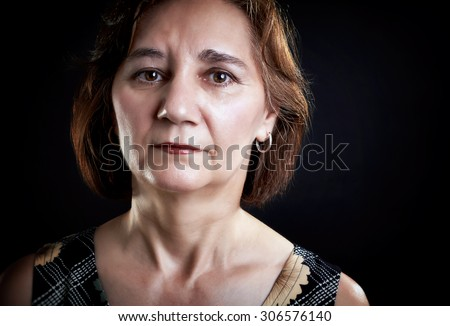 Close-up portrait of a thoughtful woman, middle aged, looking at the camera, isolated on black. - stock photo