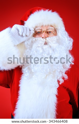 Close-up portrait of a traditional Santa Claus over red background. Studio shot. Christmas. - stock photo
