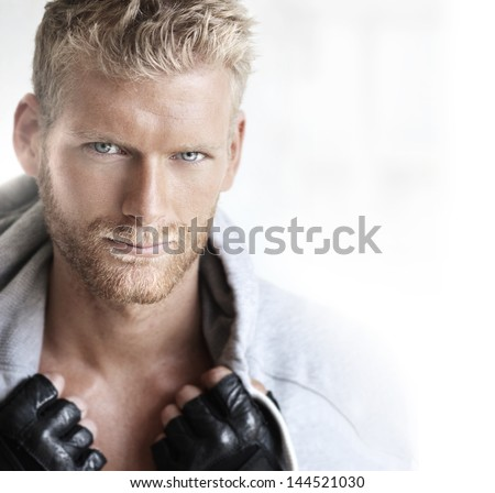 Close-up portrait of a very handsome young male model in bright studio