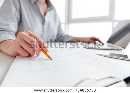 Close up portrait of a woman holding pencil over paper documents while sitting and working with laptop computer at home