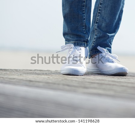 Close up portrait of a woman standing outdoors in blue jeans and comfortable white shoes