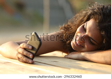 Close up portrait of a woman watching social media in a smart phone at sunset in a park table - stock photo
