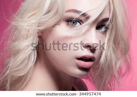 Close-up portrait of a woman with beautiful eyes and blonde hair on a pink background - stock photo