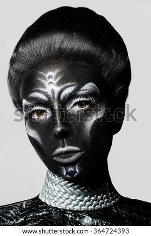 Close-up portrait of a woman with creative make-up. Black leather with white pattern.