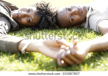 Close up portrait of a young african american couple laying down on green grass in the city, on a sunny day.
