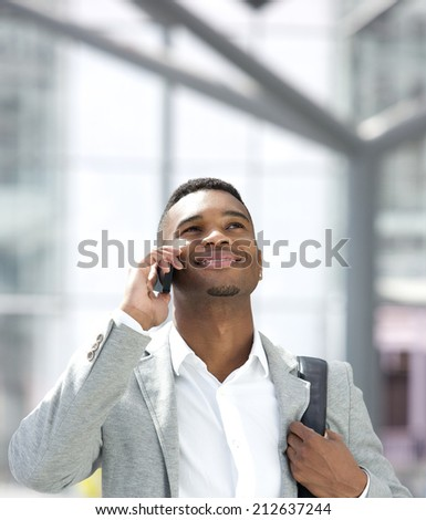 Close up portrait of a young african american man smiling with mobile phone - stock photo