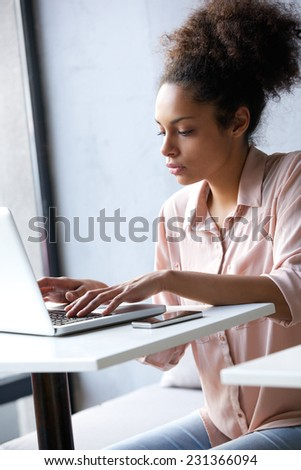Close up portrait of a young african american woman typing on laptop - stock photo