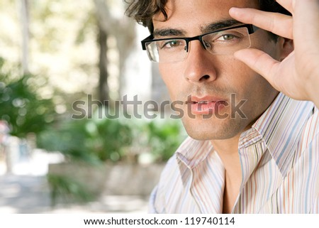 Close up portrait of a young and attractive businessman looking at the camera while holding his reading glasses with his hand. - stock photo