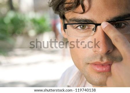 Close up portrait of a young and attractive businessman looking at the camera while holding his reading glasses with his finger. - stock photo