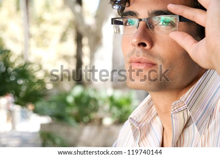 Close up portrait of a young and attractive businessman looking up while holding his reading glasses with his hand.
