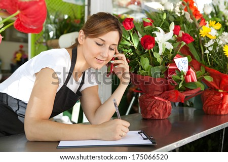 Close up portrait of a young and attractive florist business woman and shop attendant using a smartphone to take an oder over the phone during a sunny day. Working business outdoors. - stock photo