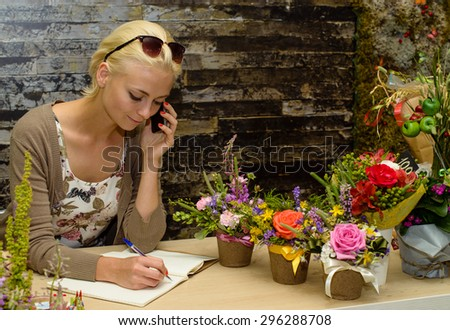 Close up portrait of a young and attractive florist business woman and shop attendant using a smartphone to take an oder over the phone. Focus on the face of the model on the left - stock photo