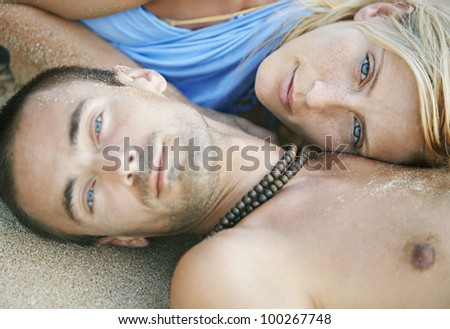 Close up portrait of a young attractive couple laying down on golden sand, the woman is resting her head on the man's chest.