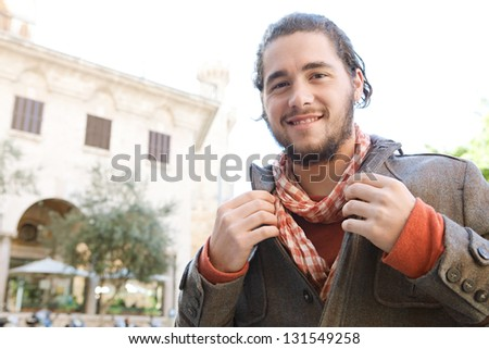 Close up portrait of a young attractive fashionable man grooming himself with a winter jacket and a scarf during a sunny day, smiling. - stock photo