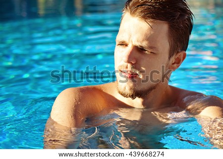 Close up portrait of a young attractive man in a swimming pool.