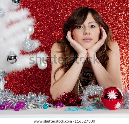Close up portrait of a young attractive woman decorating a small christmas tree sitting at a table in front of a red glitter background.