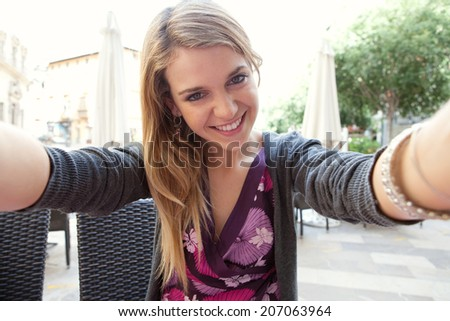 Close up portrait of a young attractive woman holding a smartphone digital camera with her hands and taking a selfie self portrait of herself while networking. Travel and technology outdoors. - stock photo