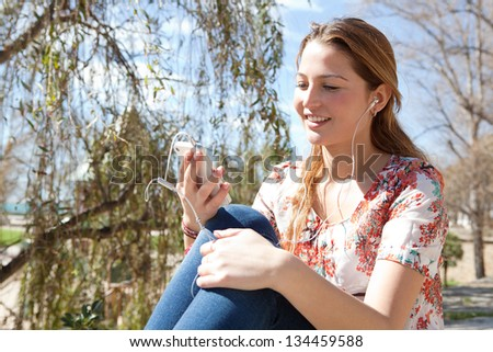 Close up portrait of a young attractive woman using a smartphone to listen to music while sitting in a park with a blue sky during a sunny day.