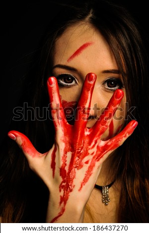 close-up portrait of a young, beautiful and emotional woman covering her face bloody hand - stock photo