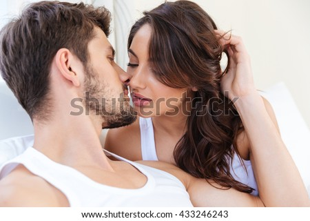 Close-up portrait of a young beautiful pretty kissing couple laying in bed