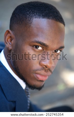 Close up portrait of a young black businessman sitting outdoors