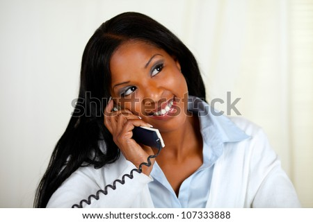 Close up portrait of a young black woman conversing on phone while is thinking and looking up - stock photo