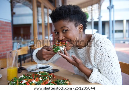 Close up portrait of a young black woman eating vegetarian pizza - stock photo