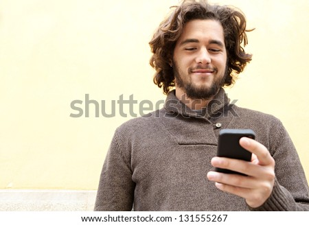 "Close up portrait of a young bohemian man using his ""smart phone"" while leaning on a yellow wall, smiling outdoors."