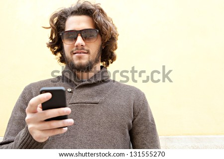 """Close up portrait of a young bohemian man using his """"smart phone"""" while leaning on a yellow wall, smiling outdoors. - stock photo"""