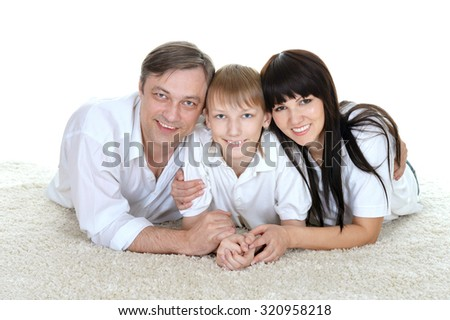 close-up portrait of a young boy and his parents lying on the floor - stock photo