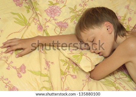 close-up portrait of a young boy sleeping in bed - stock photo