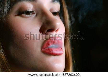 close-up portrait of a young brown-haired woman, sexy smoking hookah on a dark background Studio