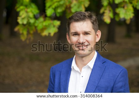 Close up portrait of a young business man in a blue suit and white shirt on the background of autumn park - stock photo