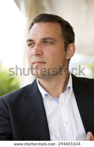 Close-up portrait of a young business man in a dark suit and white shirt  - stock photo