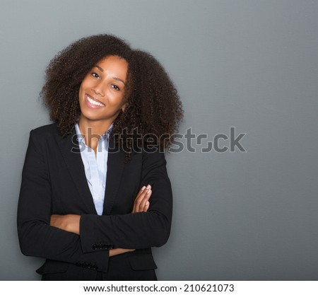 Close up portrait of a young business woman smiling with arms crossed on gray background