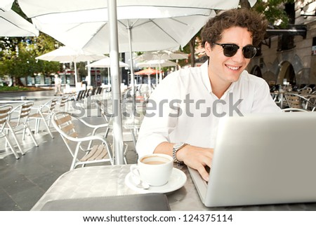 Close up portrait of a young businessman smiling and using a laptop computer while sitting outdoors at a coffee shop terrace table.