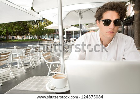 Close up portrait of a young businessman using a laptop computer while sitting at a coffee shop terrace table, outdoors.