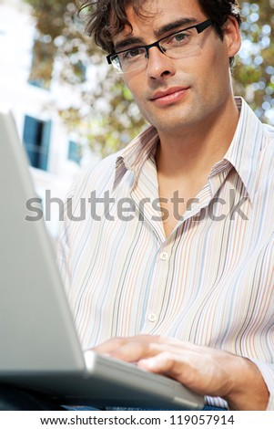 Close up portrait of a young businessman using a laptop computer while sitting on a bench in a city park, outdoors. - stock photo