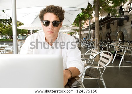 Close up portrait of a young businessman using a laptop computer while sitting outdoors at a coffee shop terrace table, outdoors. - stock photo