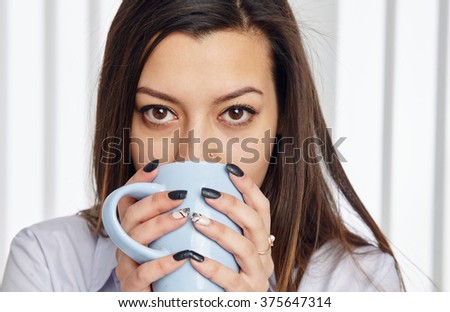 Close up portrait of a young businesswoman drinking a cup of coffee, looking at the camera. - stock photo