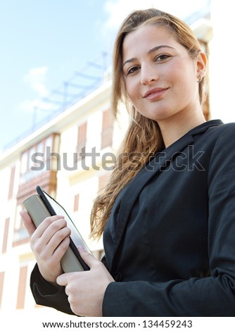 Close up portrait of a young businesswoman standing near classic office buildings in a city, carrying a digital tablet pad and a folder, smiling.