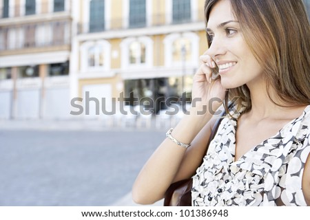 Close up portrait of a young businesswoman using a cell phone in the city, outdoors. - stock photo