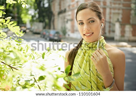 Close up portrait of a young businesswoman using an ear piece microphone to make a phone call. - stock photo