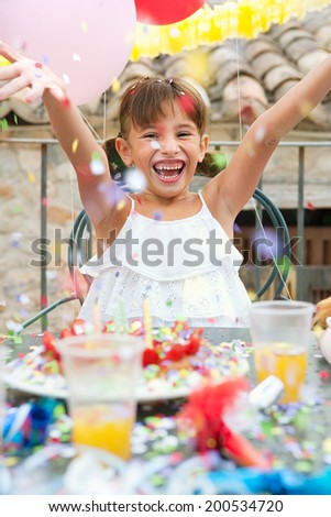 Close up portrait of a young child girl joyful expression having fun and enjoying her birthday with cake and balloons, throwing colorful confetti up and rising her arms. Family celebrations outdoors. - stock photo