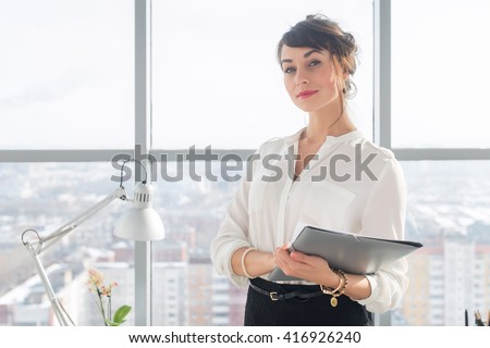 Close-up portrait of a young confident female office manager at her workplace, ready for doing business task. - stock photo