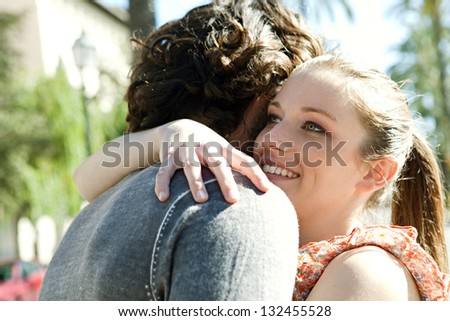 Close up portrait of a young couple on vacation hugging while visiting a destination city during a sunny day. - stock photo
