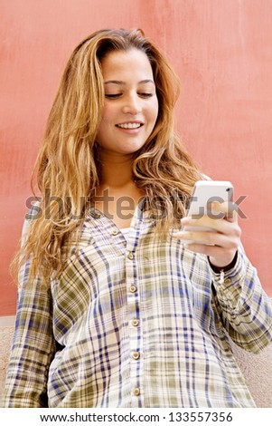 Close up portrait of a young fashionable woman holding a smartphone while leaning on a bright orange color texture wall in the city, smiling.