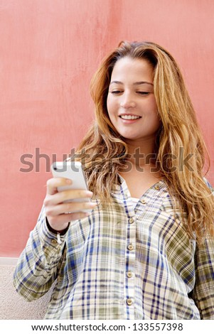 Close up portrait of a young fashionable woman holding a smartphone while leaning on a bright color texture wall in the city, smiling. - stock photo